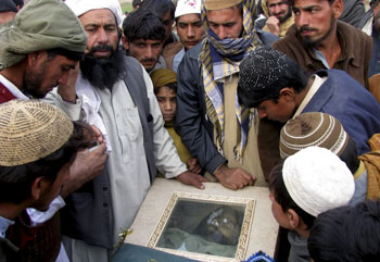 Villagers look at the body of a victim of a U.S. drone attack in December 2010, in a Pakistani tribal area along the Afghanistan border.