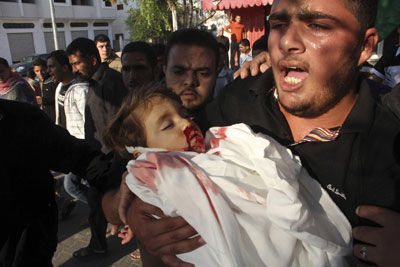 Man in Gaza, holding the body of his two-year-old child killed by an Israeli rocket