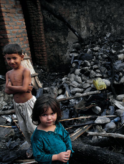 Two children standing next to home destroyed by a U.S. drone
