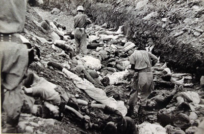 July 1950: U.S. -backed South Korean soldiers walk among thousands of political prisoners shot by South Korea at Taejon.