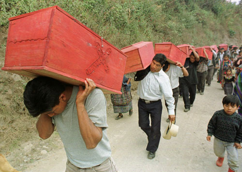 Guatemala, January 1999. Mayan men carry the coffins of victims killed by Guatemalan government in 1982, to a reburial ceremony in Xecoxol, north of Guatemala City.