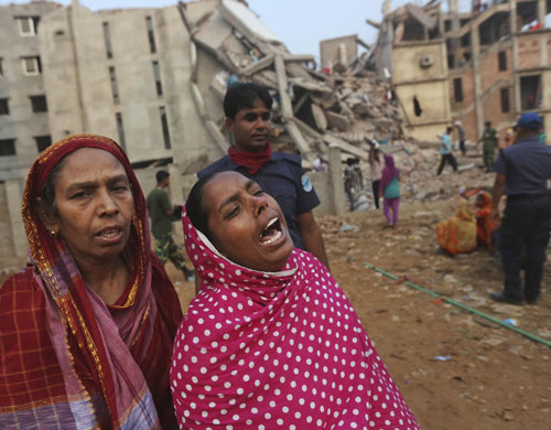 Two women grieving with collapsed factory in background.