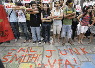 "A protest in the Philippines in  2009 after the rape of a Filipina woman by a U.S. Marine. The U.S. refused to turn the rapist over to Philippine courts citing the ""Visiting Forces Agreement"" (VFA) which provides immunity for U.S. military personnel accused of committing rape. On the protester's arms and on the ground is written ""Jail Smith"" (the Marine rapist) and ""Junk VFA."""