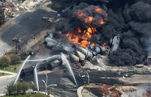 Smoke rises from derailed railway cars that were carrying crude oil out of Quebec, July 6, 2013.