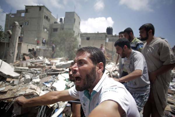 Palestinians watch as others carry a body from the rubble of a house destroyed by an Israeli missile strike in Gaza City, July 21, 2014. AP photo