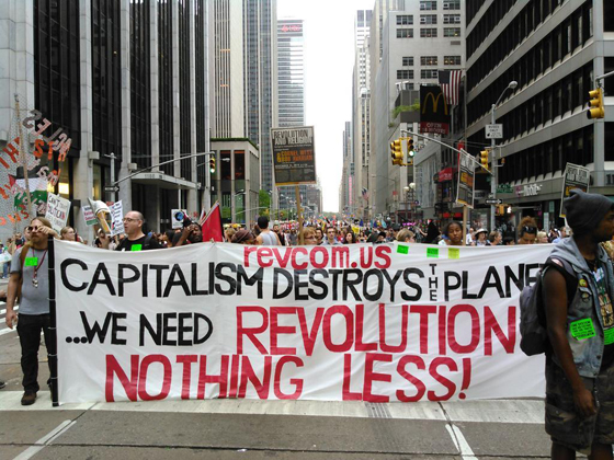 Revcom Banner at the Climate March: 9/21/14 reads Capitalism is destroys the planet We need Revolution Nothing Less