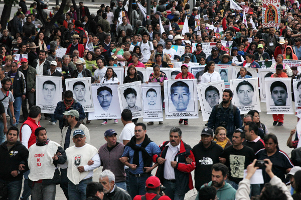 Relatives of the 43 missing students from the Isidro Burgos rural teachers college march hold pictures of their missing loved ones during a protest in Mexico City, December 26, 2014.