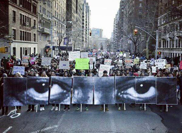 New York City, December 12, posters of the eyes of Eric Garner by French artist JR are carried in a march of thousands.