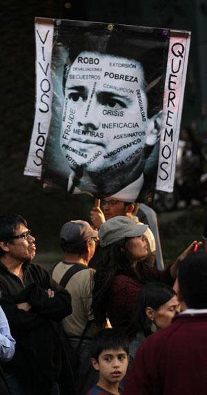 A protester holds a defaced image of Mexico's President Enrique Pena Nieto that reads in Spanish 'We want them alive' in Mexico City,, December. 6. Photo: AP
