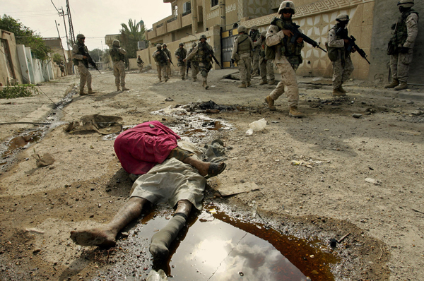 U.S. Marines walk past bodies of people killed in the U.S. assault on Fallujah, Iraq, 2004.
