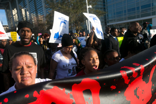 Protesters march in front of the police headquarters against the police murder of Rumain Brisbon--at center is Brisbon's 9-year-old daughter, Aiyana Rains. December 20, 2014.