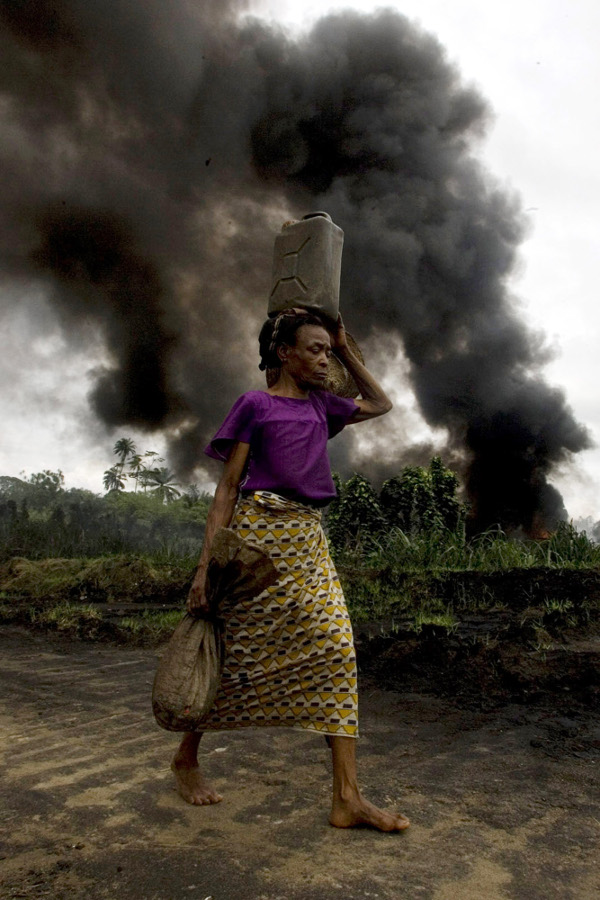 A woman walks past a burning oil pipeline in Kegbara Dere, Nigeria, in 2007. The fire burned for 45 days and 45 nights, blanketing the village with ash and torching the young cassava plants.