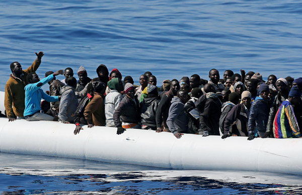 African migrants on an overcrowded inflatable dinghy who were intercepted off the coast of Libya by the Italian coast guard in April.
