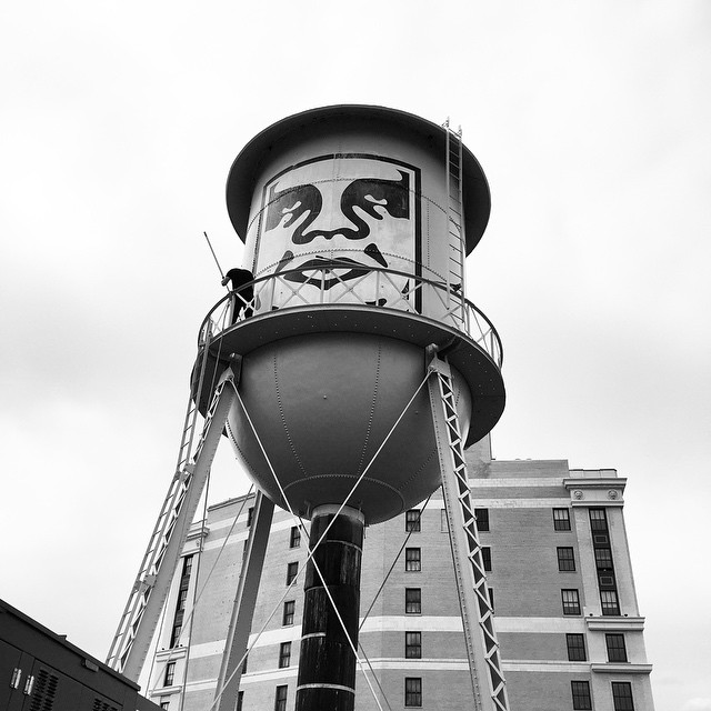 Shepard Fairey pasting up Andre the Giant on a water tower in Detroit.