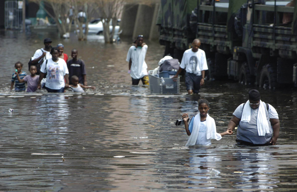 People in New Orleans who were abandoned by the system carry their possessions through the flooded streets, August 31, 2005.