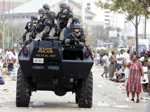 SWAT team drives past flood victims waiting at the Convention Center in New Orleans, Thursday, Sept. 1, 2005.