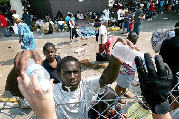 Bottles of water are handed over a fence to Hurricane Katrina victims at a temporary hospital set up at the New Orleans airport, September 3, 2005.