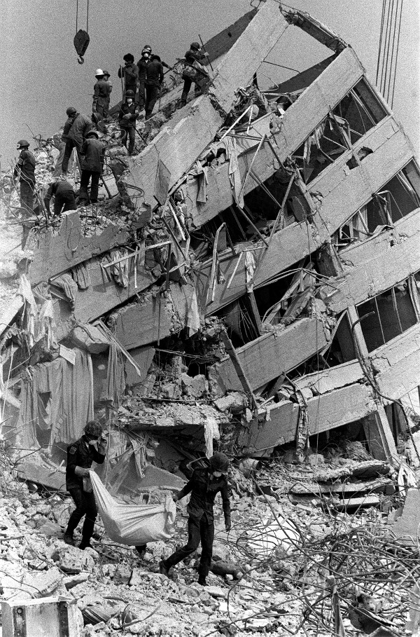 Carrying a body bag from the rubble of Mexico City's Nuevo Leon apartments, more than a week after the earthquake, September 1985.
