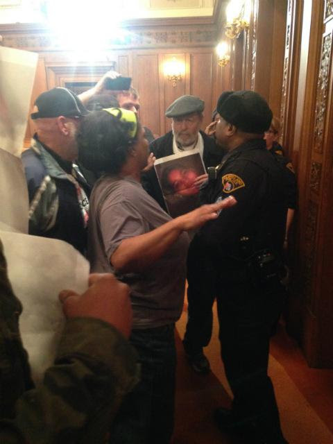 Protesters at the Cleveland City Council confront police after a member of the Revolution Club was arrested for demanding justice for Tamir Rice