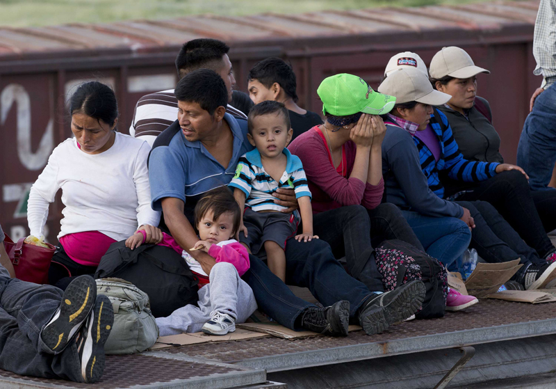 Central American families riding on top of a freight train on the way to the U.S. border