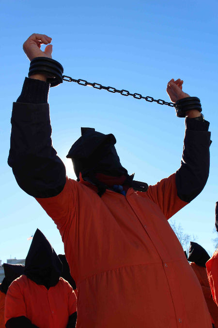 On the 14th anniversary of Guantánamo, protesters represented for the prisoners wearing orange jumpsuits and black hoods, from the White House gates to the West Coast, chanting and challenging passers-by with leaflets.