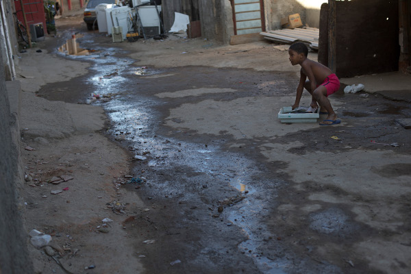 Boy playing next to sewage water slowly running through the Mandela slum in Rio de Janeiro, Brazil, August 2015.