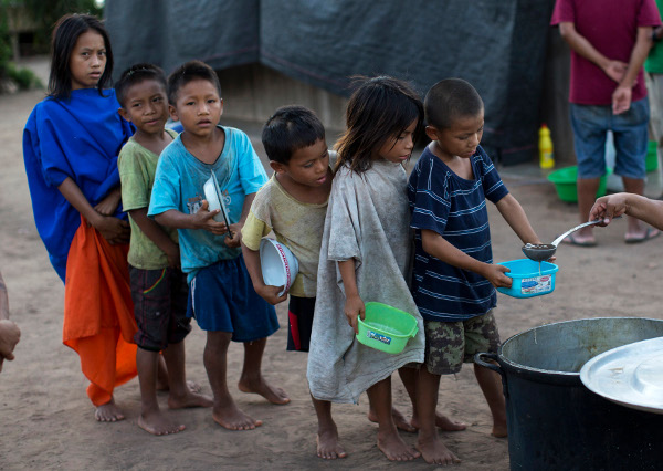 Hungry children line up to receive banana porridge in Peru, 2015. AP photo