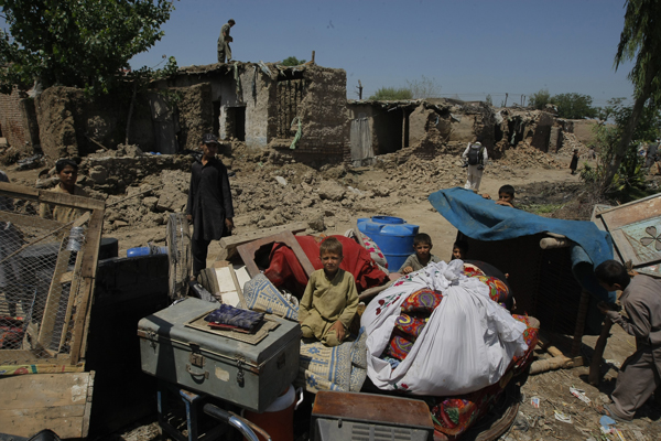 A family of Afghan refugees who fled war in their homeland collect their belongings in Peshawar, Pakistan as refugee homes are demolished by government authorities. Many refugees face deportation back to Afghanistan.