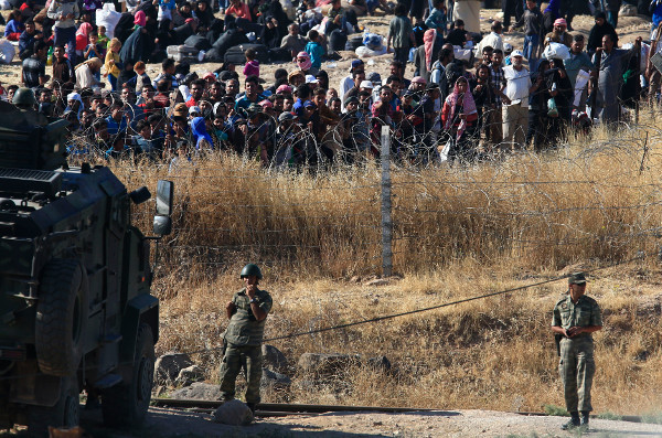 Turkish soldiers guard border as Syrian refugees wait on the Syrian side to cross, June 2015.