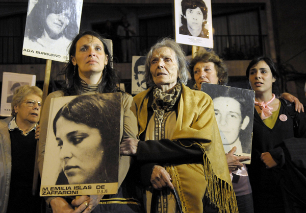 Mariana Zaffaroni Islas, front left, holds a picture of her mother during a protest in Montevideo, Uruguay in 2009.