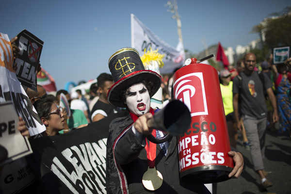 "A demonstrator in a costume depicting a banker and holding a replica of a fire extinguisher for putting out the ""flame"" of an imitation Olympic torch on the route of the Olympic torch, at the Copacabana beach, in Rio de Janeiro, Brazil, August 5."