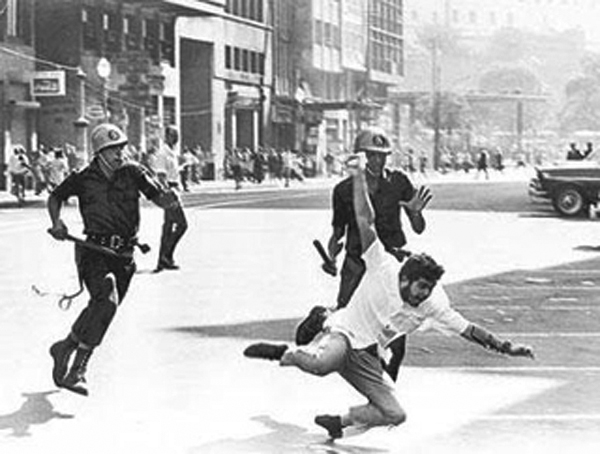A protestor against the 1964 coup in Brazil is pursued by police.