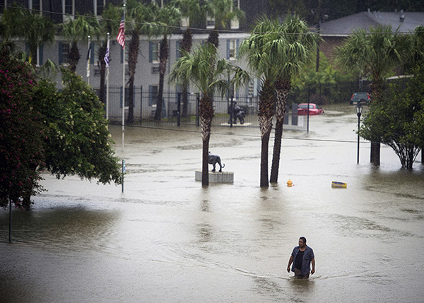 Resident wades through flood water at Tiger Manor Apartments by Louisiana State University in Baton Rouge, Aug. 13.