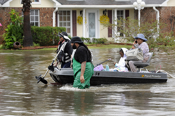 Volunteers pull a boat with a woman and young child as they evacuate from their homes, Aug. 13, 2016, in Baton Rouge