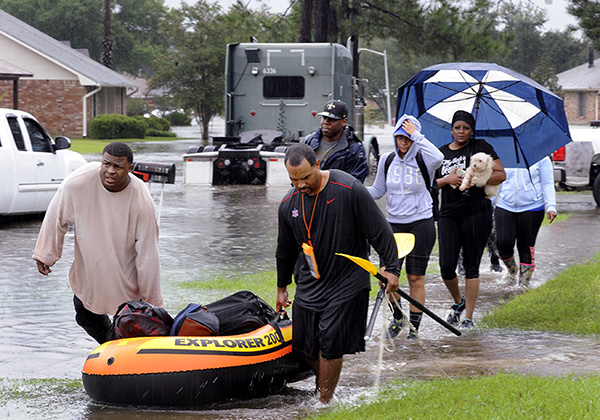 People evacuating a flooded neighborhood in Baton Rouge, Aug. 13