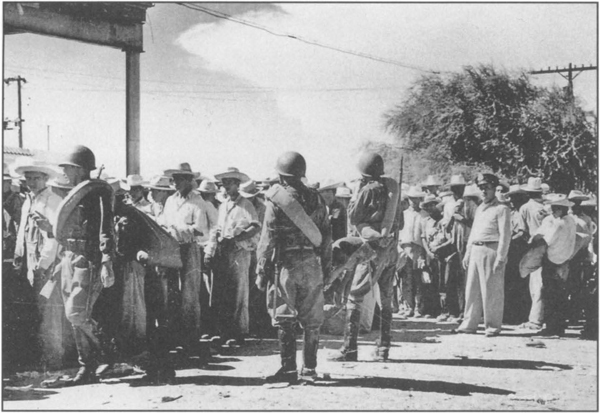 'Operation Wetback' was a U.S. government program of mass deportations of Mexican workers in the early 1950s. Above, Mexican officers guarding deportees awaiting train into Mexico at the Mexican side of the border.