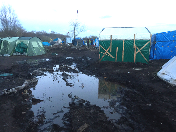 "An unauthorized camp for refugees trying to get to Britain has sprung up in Calais, France. It is called the ""Jungle"" by the authorities, who provide no services and frequently raid the camp and destroy dweillings."