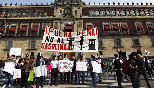 "Protesters hold a sign that reads in Spanish ""Pena Out! No to the gasoline price hike!"" January 7"