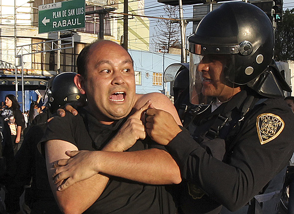 Cop removes a demonstrator who, along with others, blocked a main road for about an hour during protests against gas price hikes in Mexico City, January 4. More than 600 protesters were arrested.