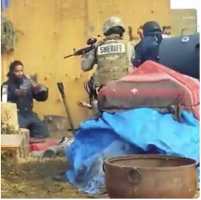 Militarized police point a gun at a Standing Rock water protector to shut down the camp.