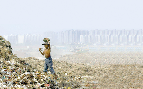 A boy in Delhi, India scavenges in a garbage dump to feed his family.
