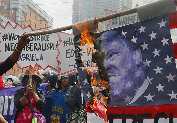In Manila, Philippines, protesters burned a U.S. flag with Trump's image on it.