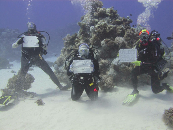 Scientists participate in March for Science underwater at Wake Atoll