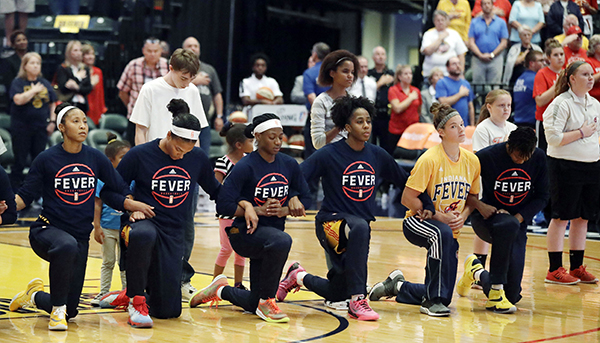 Members of the Indiana Fever kneel during the national anthem