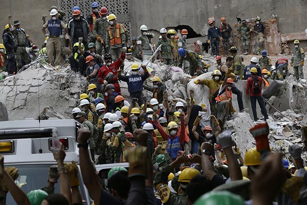 Thousands of volunteers work with professionals to remove debris of buildings collapsed by the powerful quake that hit Mexico September 19.
