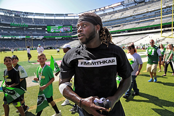 Miami Dolphin player in #IMWITHKAP T-shirt.