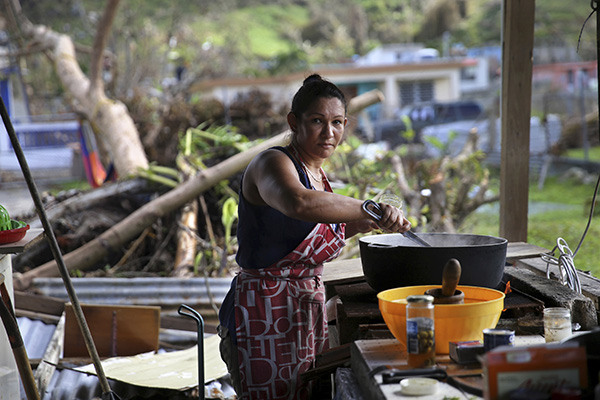 A resident of Yabucoa, Puerto Rico cooks outside over a wood fire since electric power was wiped out by Hurricane Maria