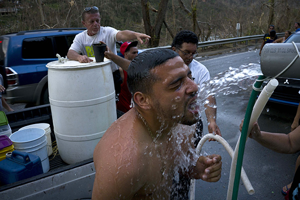 People affected by Hurricane Maria bathe in water piped from a creek in the mountains