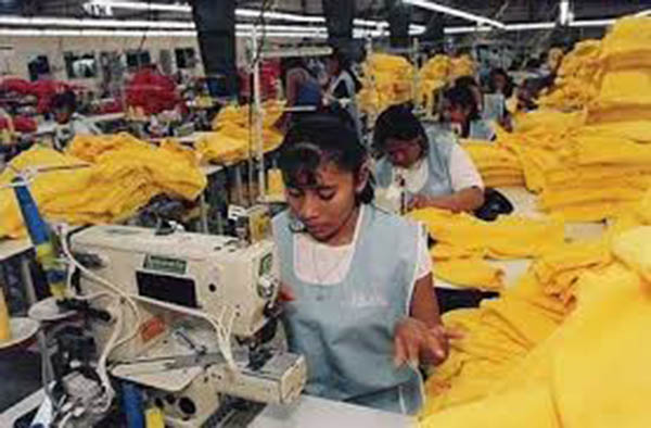 Women work in a crowded maquiladora.