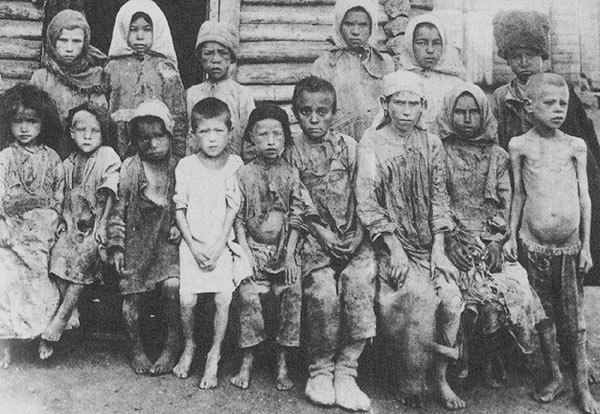 Fifteen starving children sit and stand for photo.